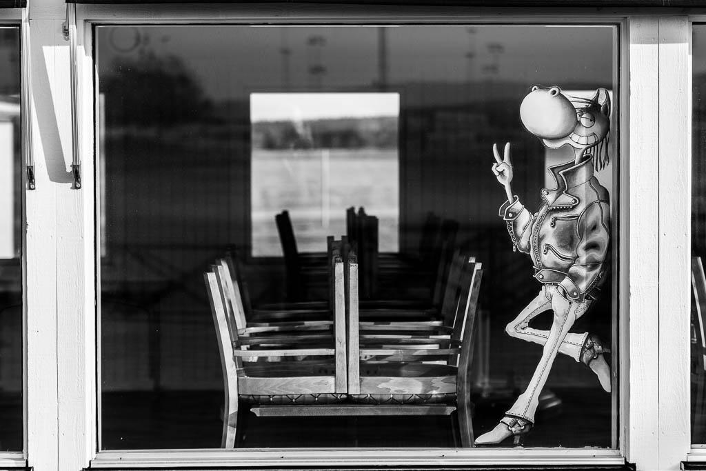 Harry Boy gör v-tecknet i ett fönster på ett stängt café.