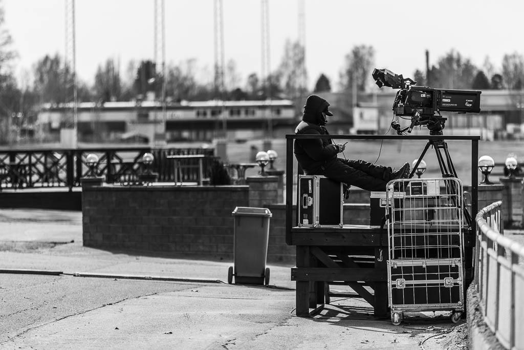 En tv-fotograf tittar på sin mobiltelefon i väntan på något att filma.